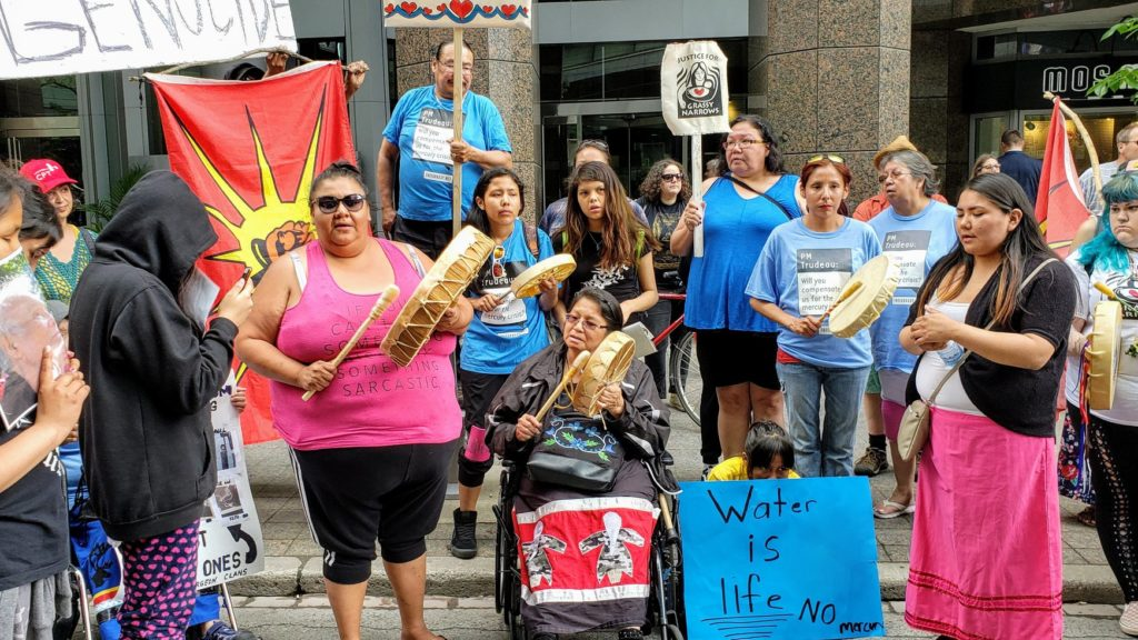 Indigenous demonstrators stand with signs and drums