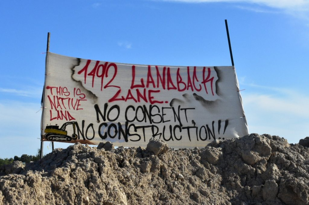 Elevated banner that reads: 1492 Landback lane. No consent, no construction. This is native land.