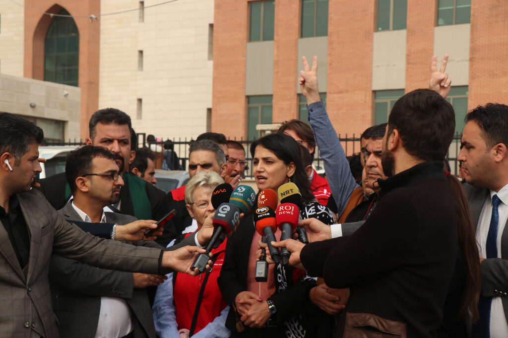 Woman speaking to media surrounded by journalists and microphones